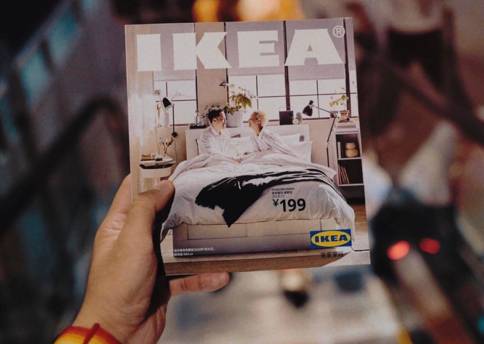 Person holding an IKEA magazine with their left hand